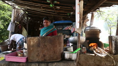 Man and woman behind the pots in outdoor kitchen in Hampi. Stock Footage