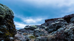 Dark clouds moving over mossy lava field at ground level evening Iceland 4k Stock Footage