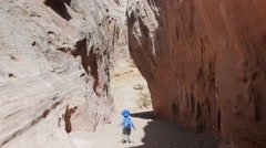 Boy runs in cool desert canyon and falls Stock Footage
