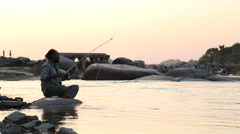 Stock Video Footage of Man sitting on rock at the riverbank and catching fish with rod.