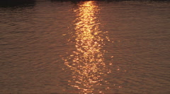 Golden reflection from sun, ripples in water Stock Footage