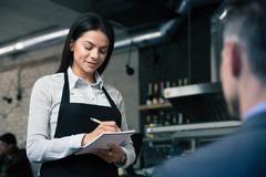 Female waiter in apron writing order Stock Photos