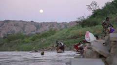 People bathing on the riverbank in Hampi at sunset. Stock Footage