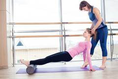 Aerobics Pilates personal trainer helping women group in a gym class Stock Photos