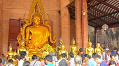Buddhist worshippers giving offerings and praying to statues Stock Footage