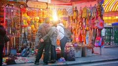 HONG KONG, CHINA - Customers browsing a vendor's wares at a the Jade Market Stock Footage
