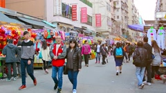 Shoppers strolling through a busy, outdoor, downtown market, in Hong Kong Stock Footage
