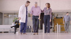 4K Caring doctor assisting patient walking with crutches in busy modern hospital Stock Footage
