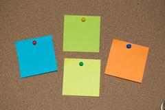 Multi Coloured Post it Notes on a Cork Board Stock Photos