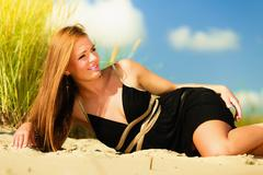 Woman sunbathing on beach. Stock Photos