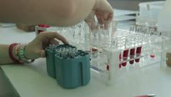 Technician packing blood samples in test tubes for laboratory analysis, close up - stock footage