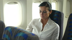 Business woman using tablet on plane Stock Footage