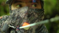 Closeup of hunter as he takes aim and releases arrow in the forest. - stock footage