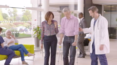 4K Caring doctor assisting patient walking with crutches in busy modern hospital - stock footage