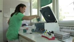 Young female medic technician takes out blood samples from machine for analyses. Stock Footage