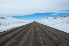 Gravel road and winter landscape - stock photo
