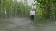 Man is aproaching in the foggy forest Stock Footage