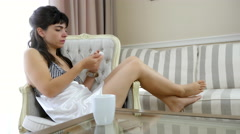 Woman in a nightdress is talking on mobile phone at home Stock Footage