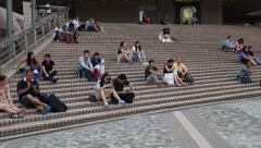 Tourists rest on the stairs in the area the Kowloon Public Pier, Hong Kong Stock Footage