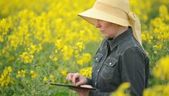 Female Farmer using Digital Tablet Computer in Rapeseed Cultivated Field - stock footage