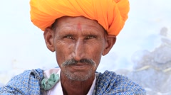 Indian man, sits on the ghat along the sacred Sarovar lake. Pushkar Stock Footage