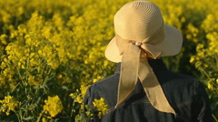 Female Farmer from Behind Walking in Oilseed Rapeseed Agricultural Field Stock Footage