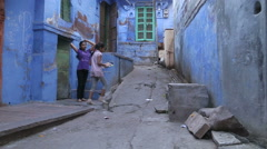 Two girls climbing on stairs in front of a house on the street of Jodhpur. Stock Footage