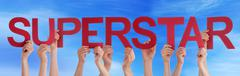 Hands Holding Red Straight Word Superstar Blue Sky - stock photo