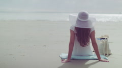 Young woman sitting on the beach relaxes in slow motion - stock footage