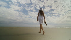 Young woman walking on the sandy beach in slow motion - stock footage