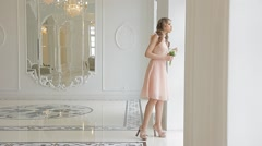 Attractive woman (bride) with a bouquet of flowers in a luxurious room. - stock footage