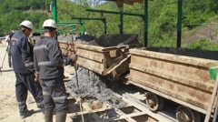 Miners unload  zinc and lead ore from wagon Stock Footage