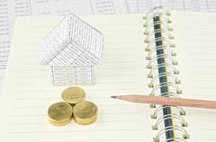 Pencil on notebook with gold coin and house Stock Photos