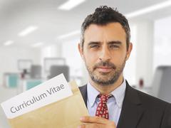 Man inside an office holding CV papers and job application documents Stock Photos