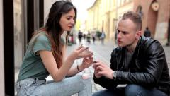 Brown hair girl sitting on the street and talking with boy (36) Stock Footage