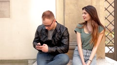 Woman and man sitting on the street. He is focused on his phone. (48) Stock Footage
