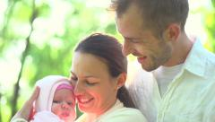 Happy family with little baby outdoors. Mother, father kissing newborn baby. Stock Footage