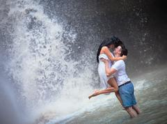 beautiful couple travels to asia at waterfall - stock photo