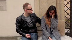 Girl sitting on the stone wall next to the boy in glasses, she is crying Stock Footage