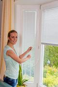 woman lowers blinds - stock photo