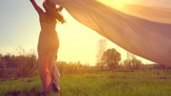 Girl in long dress with chiffon scarf running on summer field and raising hands Stock Footage