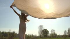 Beauty girl in long dress with chiffon scarf running on summer field to sunset - stock footage