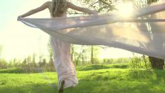 Stock Video Footage of Girl in long dress with chiffon scarf running on summer field to sunset