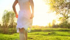 Beauty girl in white dress running on spring field to sunset and raising hands. Stock Footage