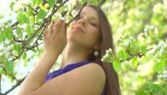 Stock Video Footage of Beautiful young woman enjoying nature outdoor. Flowers on trees.