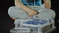 child collects toy sport Stadium close shot slider black background - stock footage