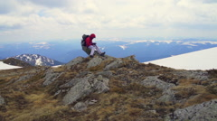 hiker sitting on the rocks against the mountain lanscape - stock footage