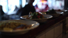 Waiter taking dishes from kitchen, close up, shallow focus Stock Footage