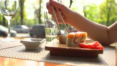 Happy couple eating sushi rolls in japan restaurant, sushi bar. Dinner. Stock Footage