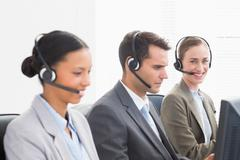 Business people with headsets using computers - stock photo